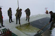 Rybáři prořezávají led na rybníce Koclířov.